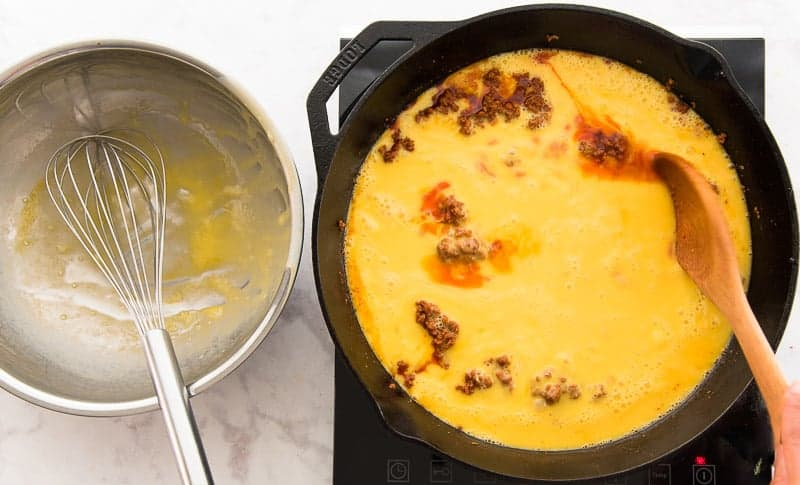 The eggs are added to the cooked chorizo in the skillet