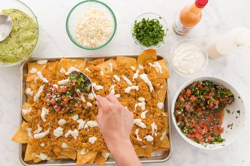 Pico de gallo and other toppings are spooned onto the nachos