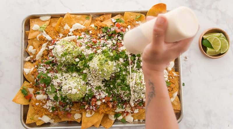 Crema is drizzled from a squeeze bottle onto the nachos