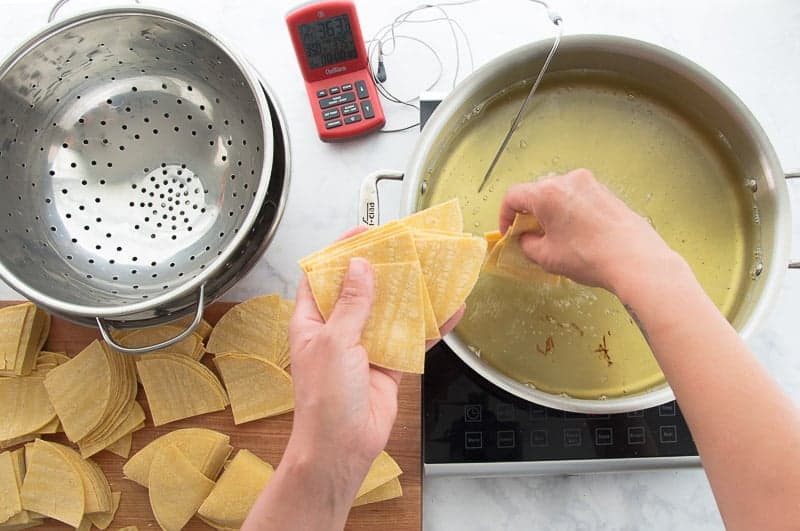 A hand adds corn tortilla triangles to hot frying oil