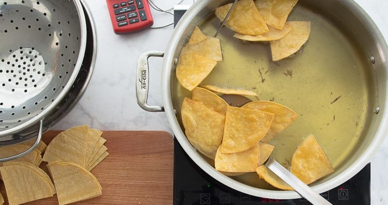 A spider lifts the fried corn tortilla chips from a pot of frying oil