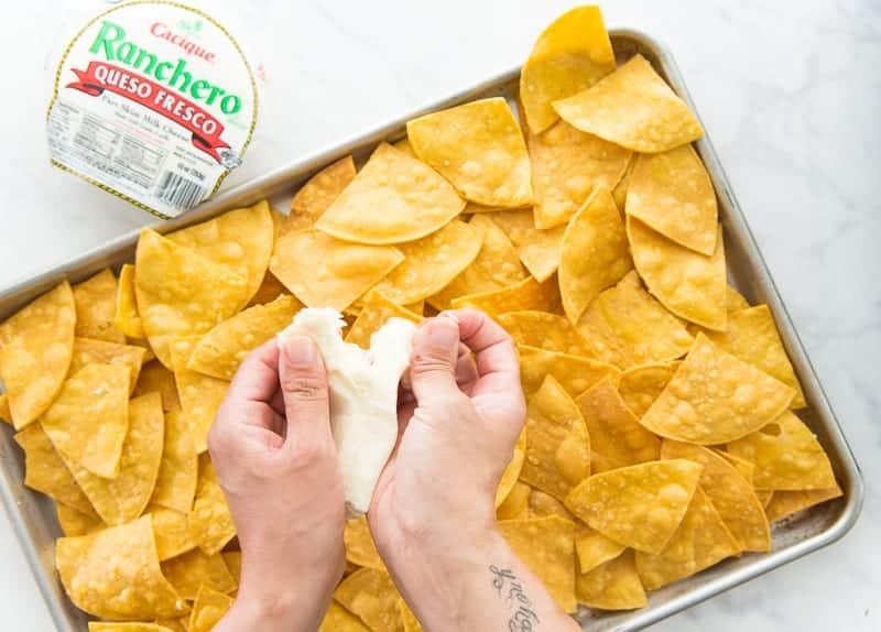 A hand shreds queso fresco cheese over a bed of warmed tortilla chips