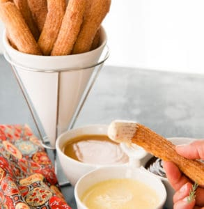 A churro is dipped into the Crème Anglaise (Warm Vanilla Bean Sauce)