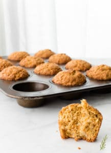 An Oatmeal Carrot Cake Muffin with a bite taken out of it sits in front of a muffin tin filled with muffins