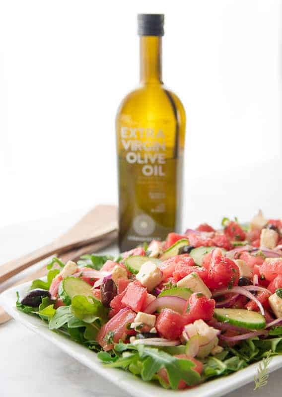 Side view of salad on a platter with olive oil in background
