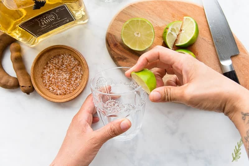 Rubbing lime juice onto the rim of the cocktail glass