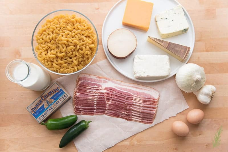 The ingredients needed for the Ultimate Bacon-Jalapeño Mac and Cheese. A plate full of cheeses, a bottle of milk, bacon, jalapeños, Danish Creamery butter, eggs, onion, and garlic