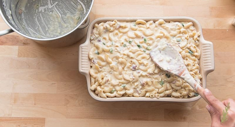 Smoothing the unbaked mac and cheese into the casserole dish prior to baking