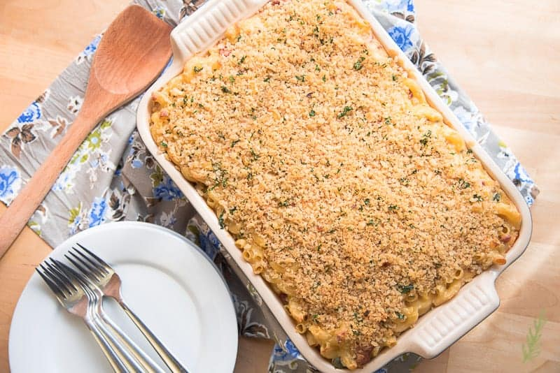 Overhead shot of casserole dish filled with mac and cheese. Wooden spoon and stack of plates with forks on top.