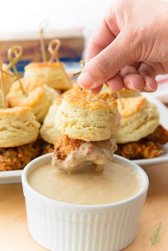Dipping a skewer with chicken and biscuit into the maple-butter dipping sauce
