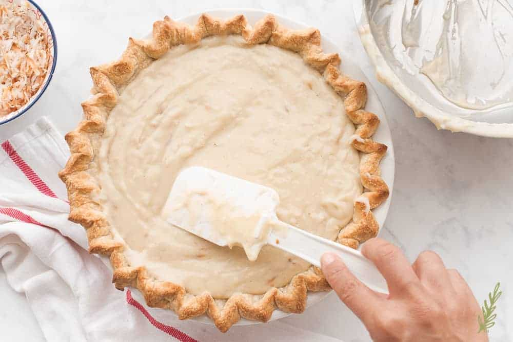 Smoothing the coconut-rum custard into the baked pie shell