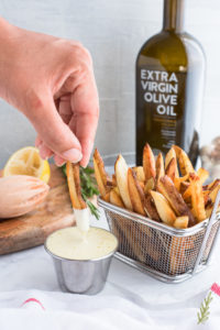 Hand dipping a fry into the lemon aioli dip