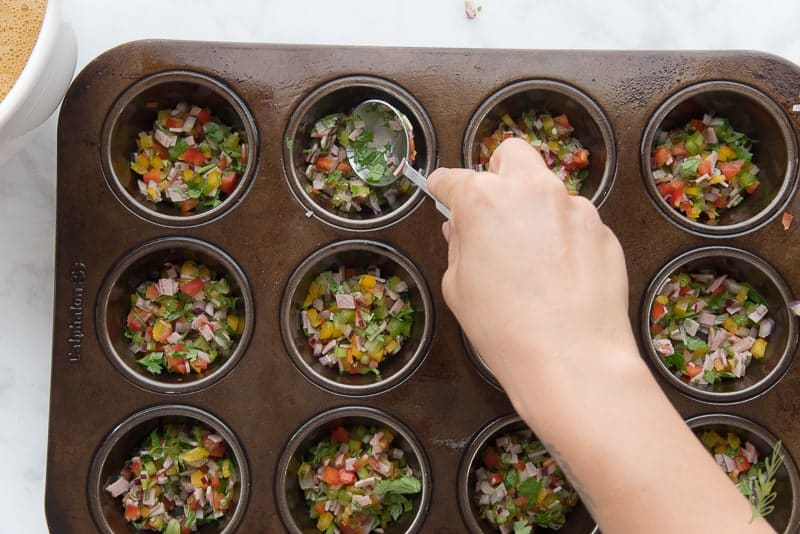 Portioning the veggie-ham mix into each muffin cup
