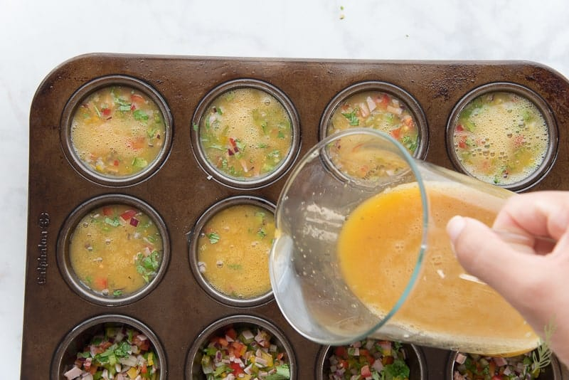 Pouring the beaten eggs into the muffin tin