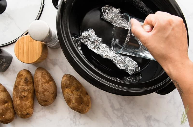 Pouring water into the slow cooker for the Make Ahead Western Omelets w SC Baked Potatoes