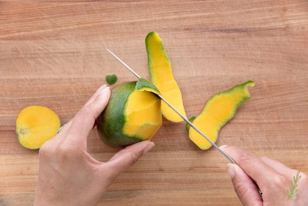 Removing the peel from a mango using a chef's knife