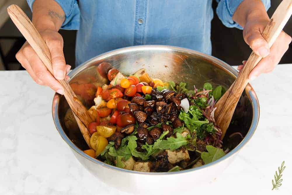 Tossing the salad together in the balsamic vinaigrette