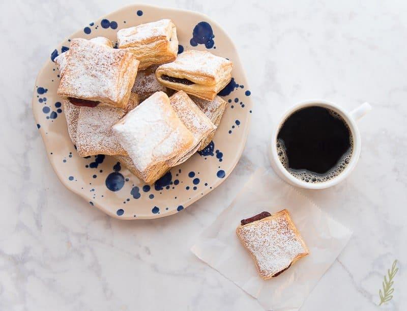 Overhead shot of pastelillo de guayaba, a plate of pastelillos de guayaba and a mug of coffee