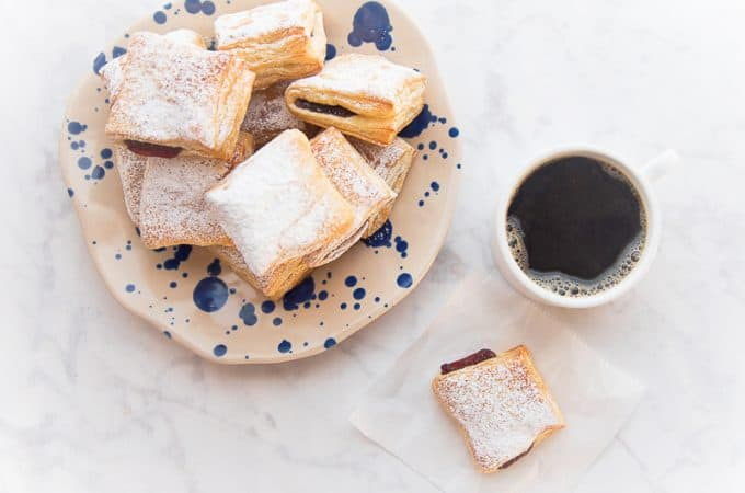 FB Image overhead shot of pastelillo de guayaba, a plate of pastelillos de guayaba and a mug of coffee