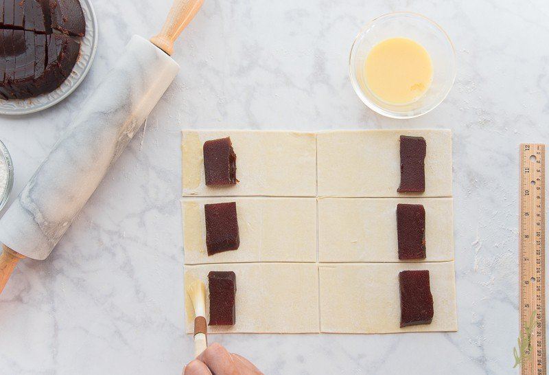 Brush the egg wash on the short side of the puff pastry rectangle