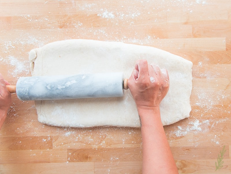 Gently rolling out the puff pastry dough to begin the folding in process