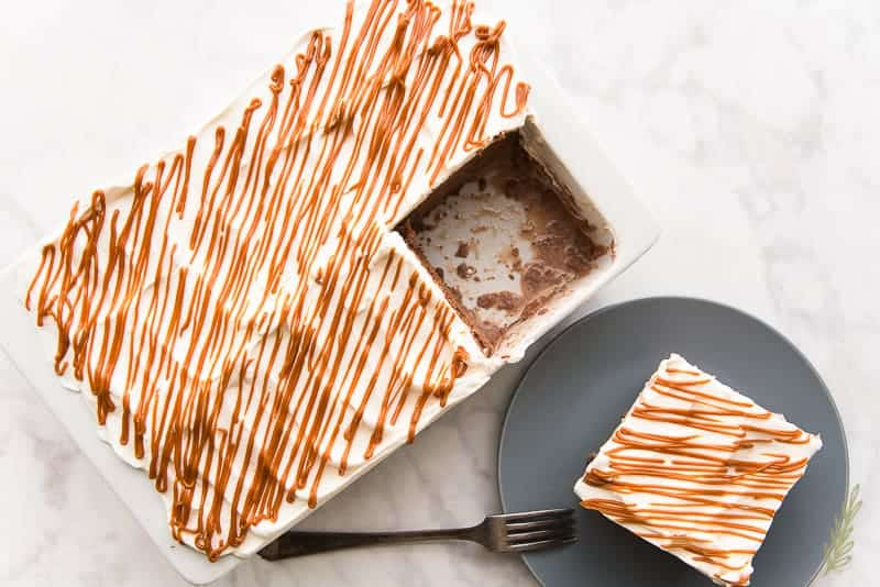 A pan of frosted tres leches with a slice removed