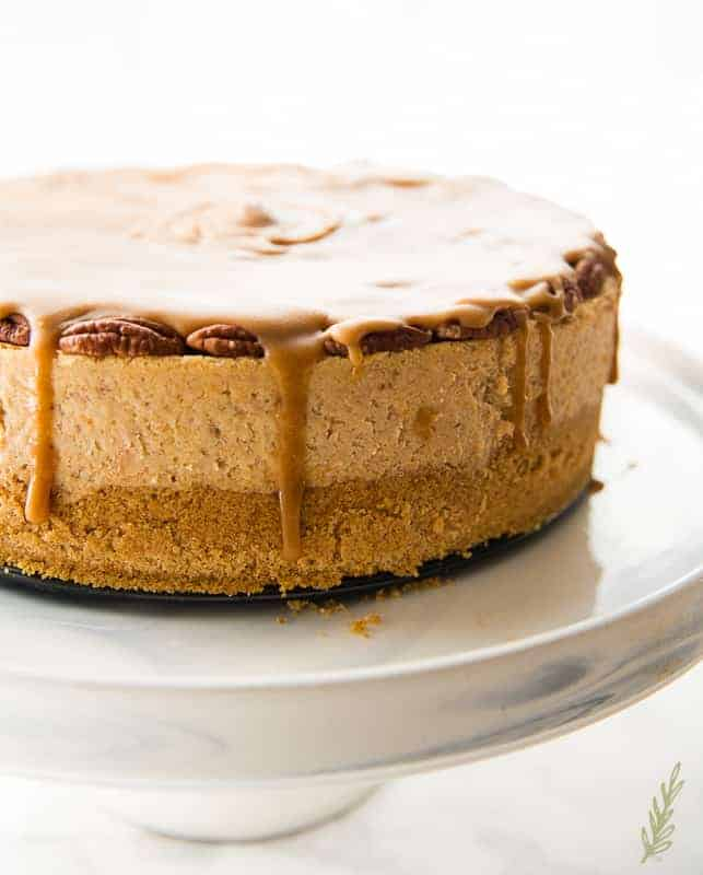 A side view of the Sweet Potato Cheesecake with Pecan Praline Topping after being topped with the praline topping