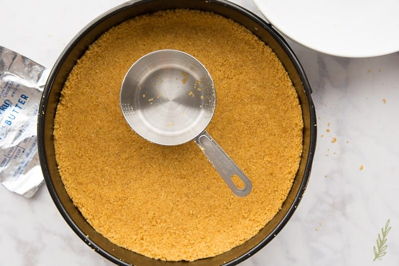 Press the graham cracker mixture into the pan to create the crust