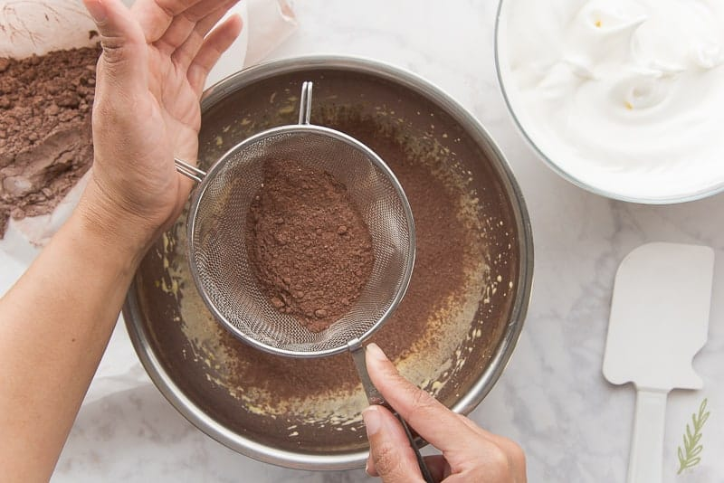Sift half of the dry ingredients into the whipped egg yolks