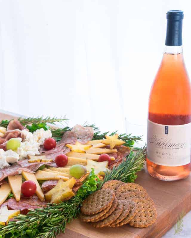 The finished Festive Charcuterie Board- complete with a glass of wine- is a great centerpiece for your festivites
