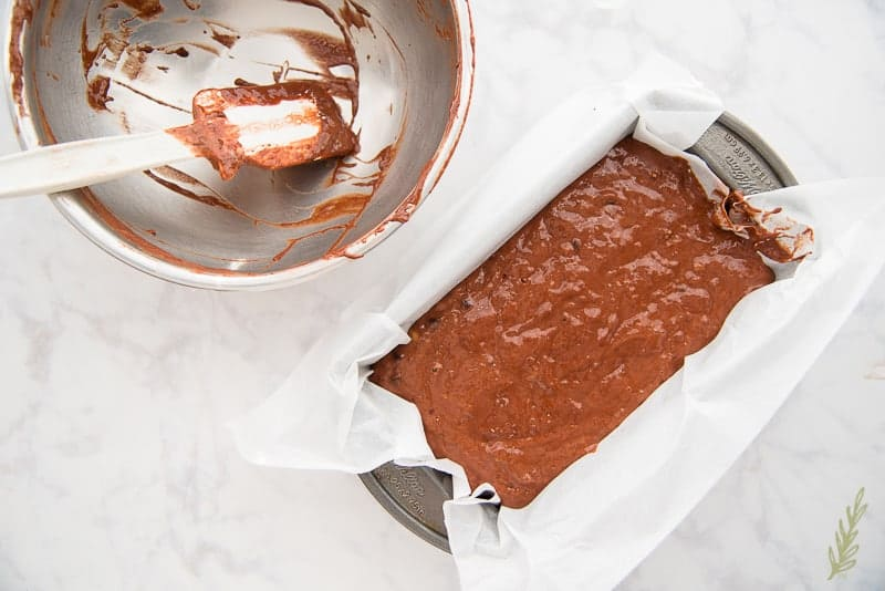 Scrape the Mint Chocolate Chip Banana Bread batter into the parchment-lined loaf pan