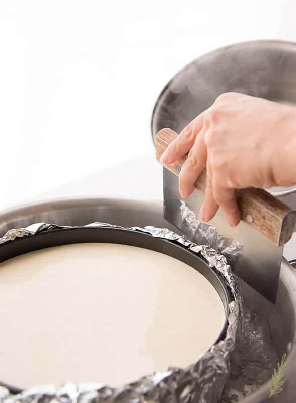 Add boiling water to the larger pan to bake the Creamy Coquito Cheesecake