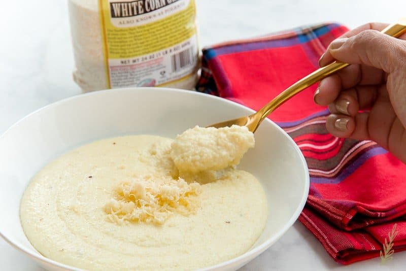 A white bowl full of Cheesy Grits with Garlic a hand is taking a spoonful from the bowl
