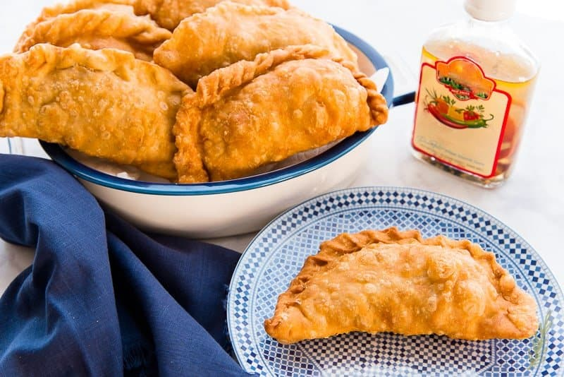 A flaky Pork Picadillo Empanada on a blue plate