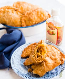A plate of Pork Picadillo Empanadas, one is broken in half to reveal filling