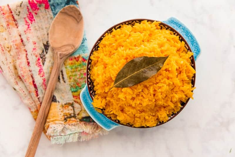 Overhead shot of the Arroz Borracho in a blue blue next to wooden spoons.