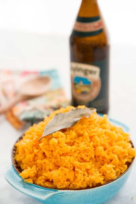 A teal bowl is filled with Arroz Borracho and topped with a bay leaf. The beer sits in the background