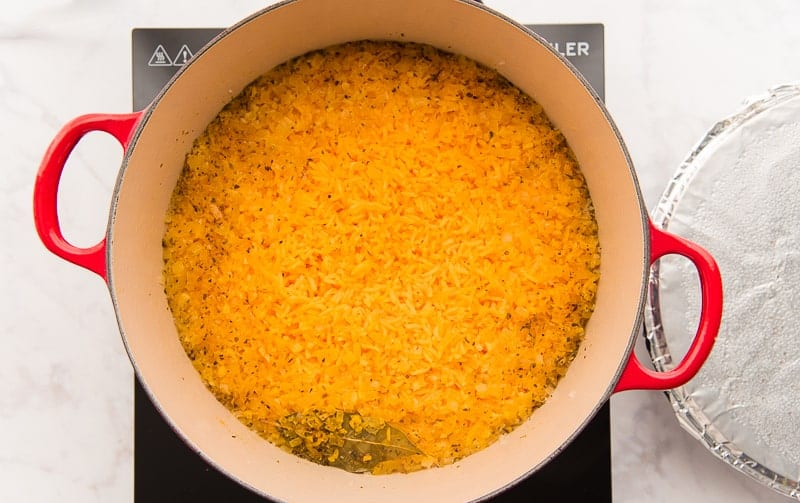 An overhead image of the yellow Arroz Borracho in a red pot.