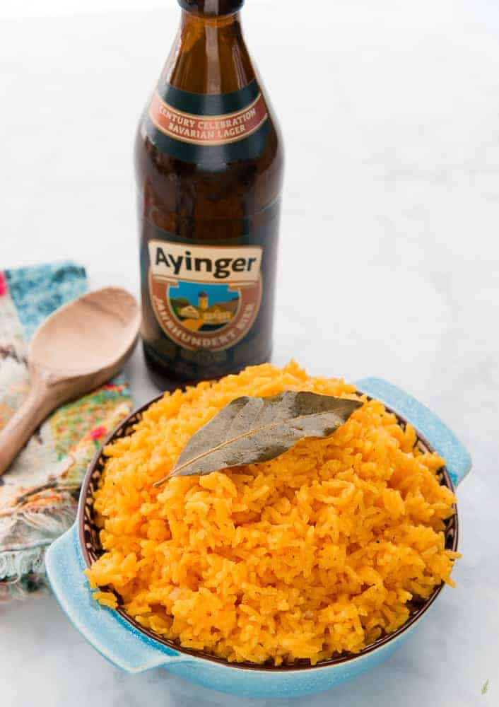 A 3/4 view of a bowl filled with Arroz Borracho. A bottle of lager sits in the background.