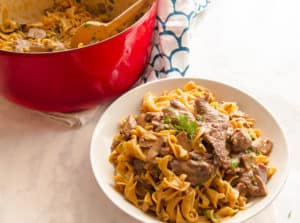 On overhead shot of One-Pot Beef Stroganoff in a white bowl with the red pot behind