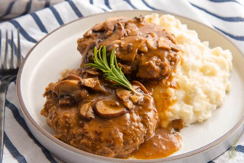 A close up of the Salisbury Steak with a sprig of thyme on top