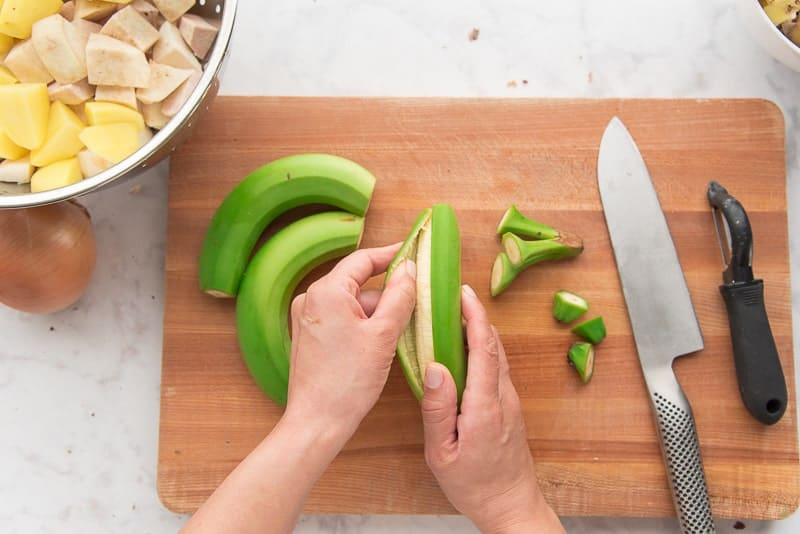 Peeling off the skin of the green bananas