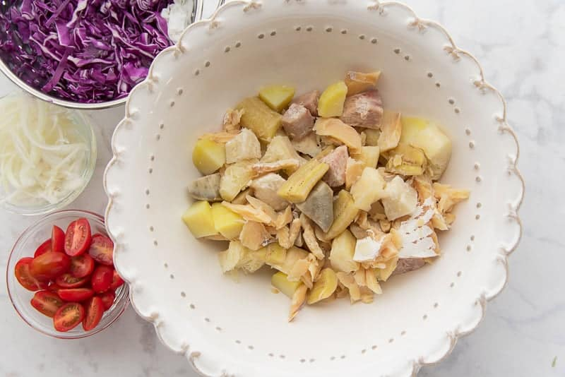 The boiled codfish and root veggies are put into a large mixing bowl.