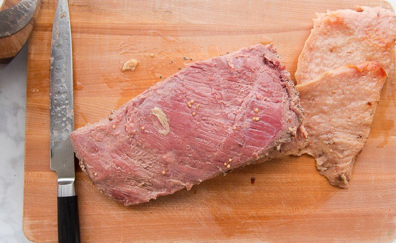Remove the fat from the corned beef before cutting against the grain