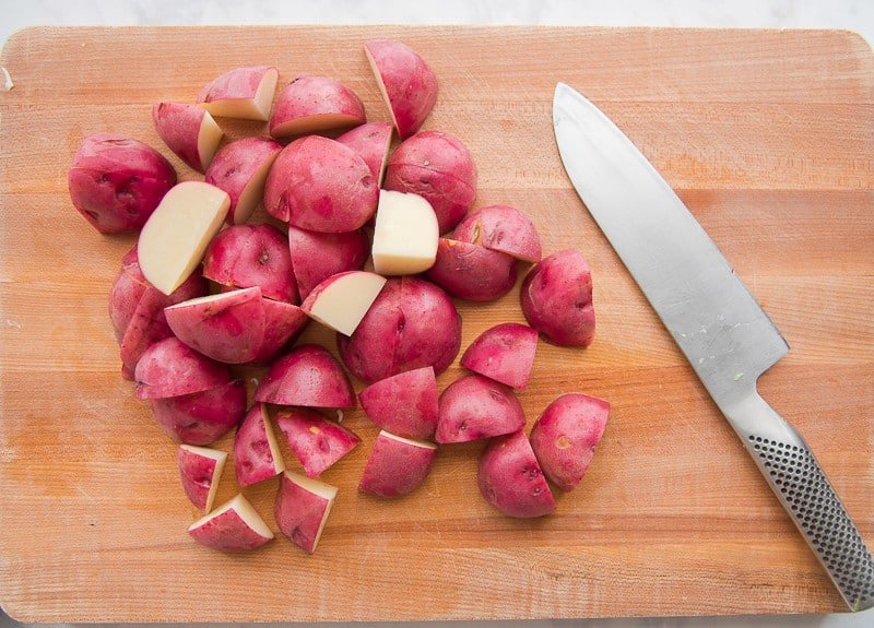 Cut the red potatoes into quarters before adding to the Baked Corned Beef and Cabbage