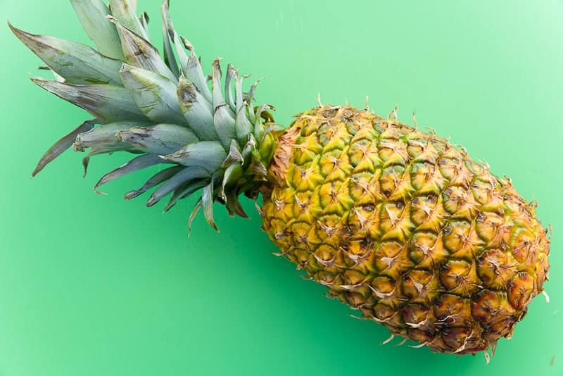 A pineapple lays on its side on a green cutting board