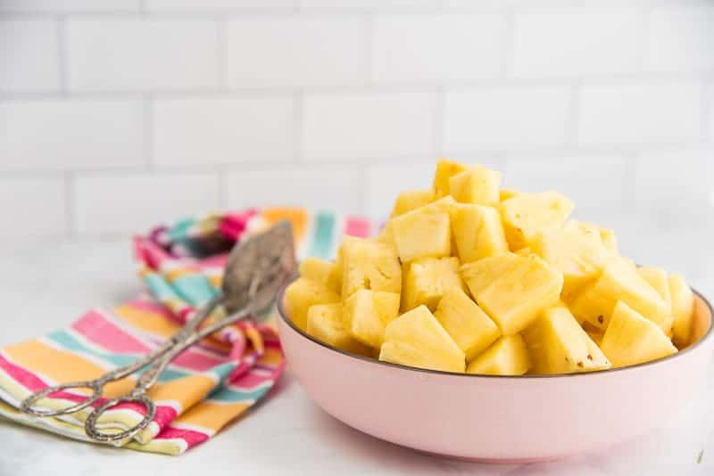 A side view image of a pink bowl filled with cut pineapple. A pair of tongs sits next to the bowl on a striped kitchen towel