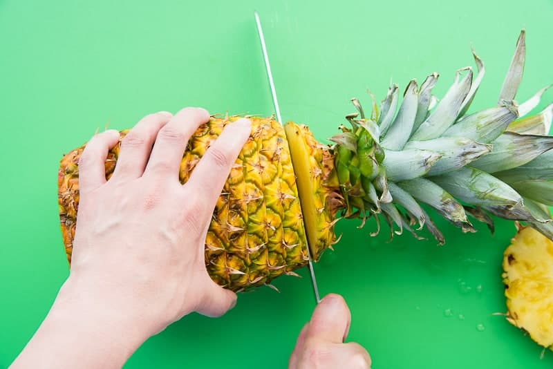 A hand holds the pineapple while the other cuts the top and bottom off
