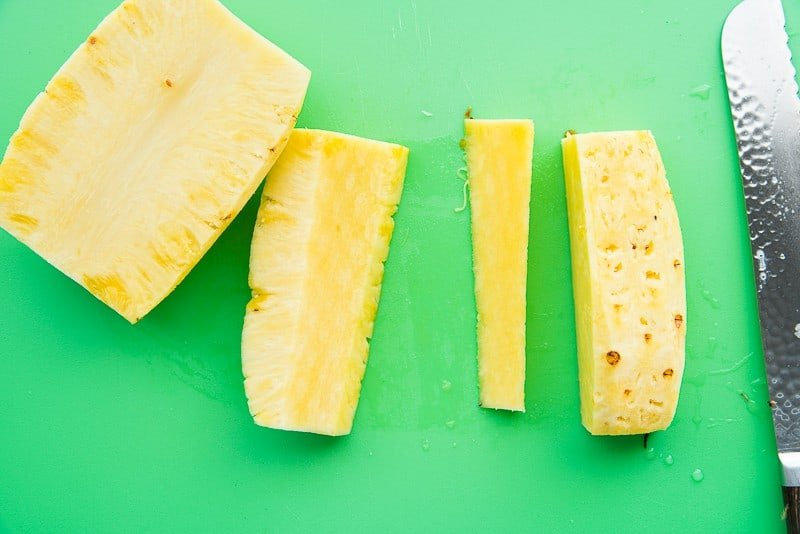 A section of pineapple with its core removed sits on a green cutting board a knife is to the right
