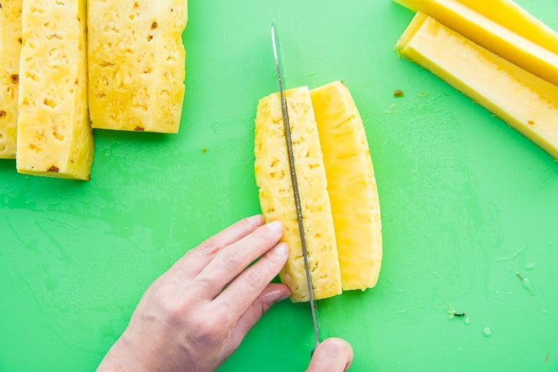 A knife slices pineapple quarters into three sections on a green cutting board